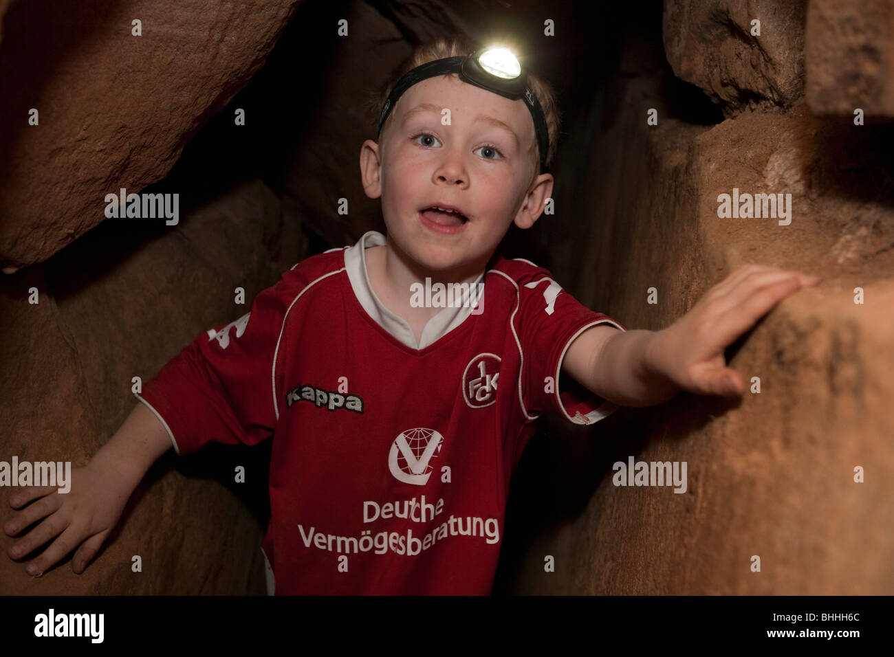 Little boy with headlamp inside of a cave near Neustadt, Palatinate, Germany - Stock Image