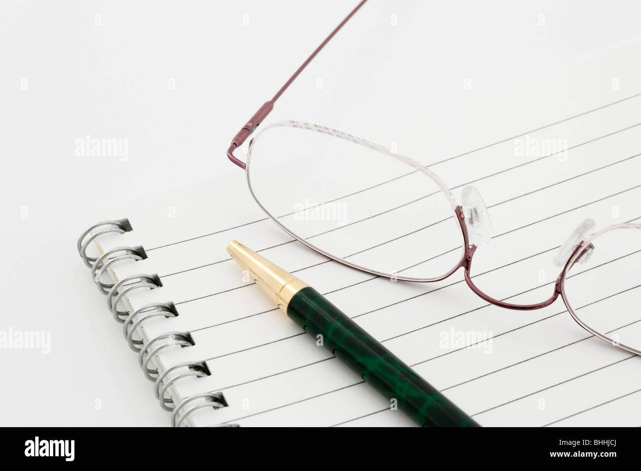 Close-up of a blank lined paper spiral bound notebook notepad with a ballpoint pen and a pair of spectacles on a - Stock Image