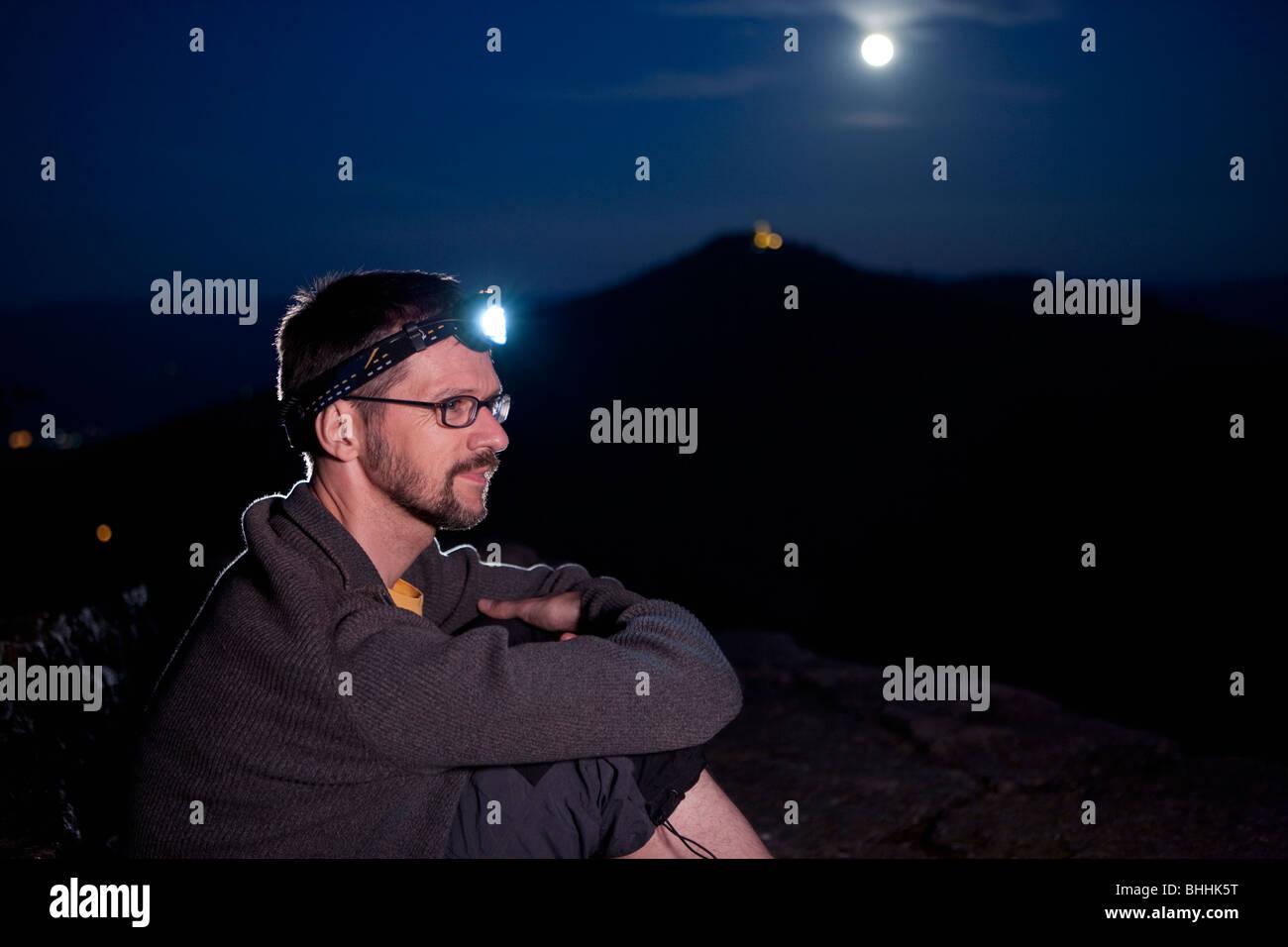 Sitting rock climber wearing headlamp on Battert Rocks near Baden-Baden at night, Baden-Wuerttemberg, Germany - Stock Image