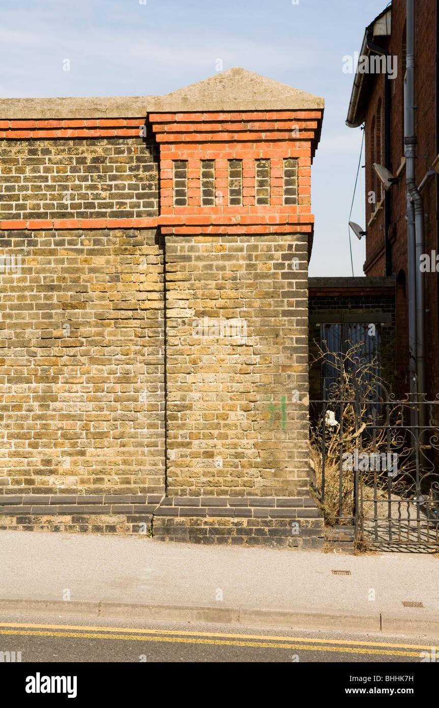Ornamental brick pillar at the end of a large brick wall - Stock Image