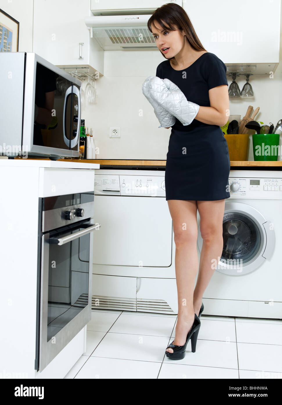 beautiful caucasian woman in a kitchen waiting with anxiety in front of the oven - Stock Image