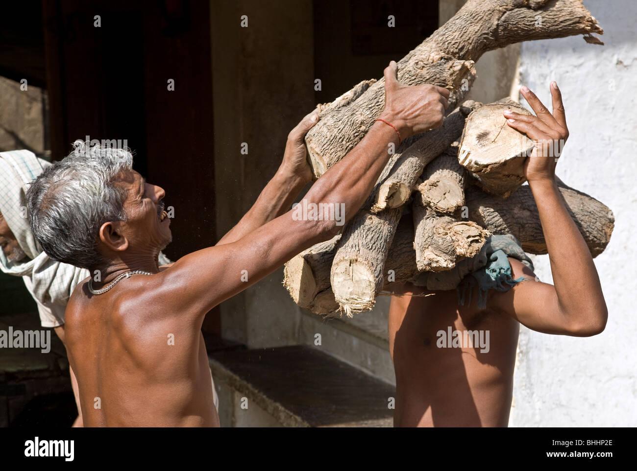 Outcast men carrying wood for the ritual corpse cremation. Manikarnika Ghat. Varanasi. India - Stock Image