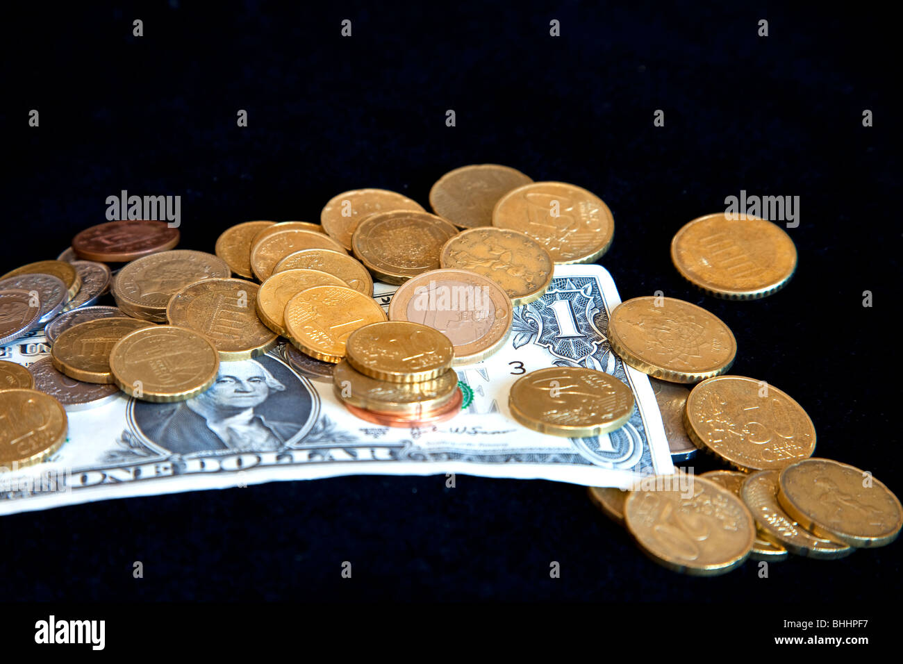 Euro coins on a US dollar with a black background - Stock Image