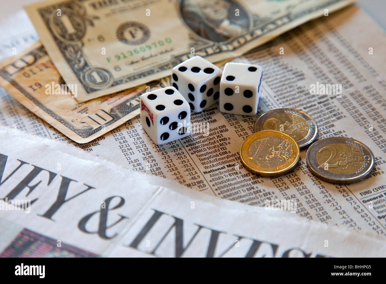 US dollars, Euro coins, dice and investment paper - Stock Image