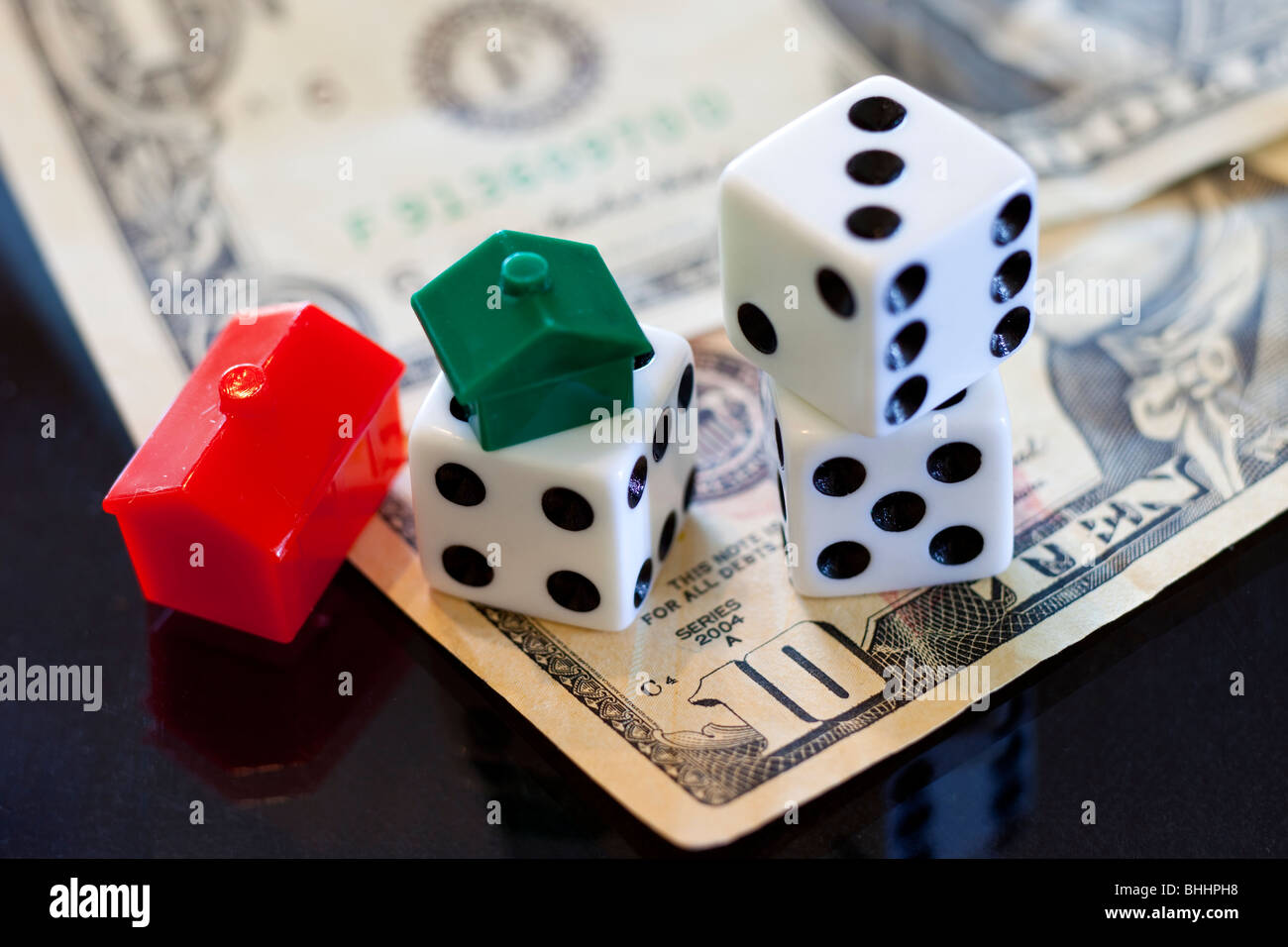 US dollars, Dice and Monopoly house and hotel on black background - Stock Image