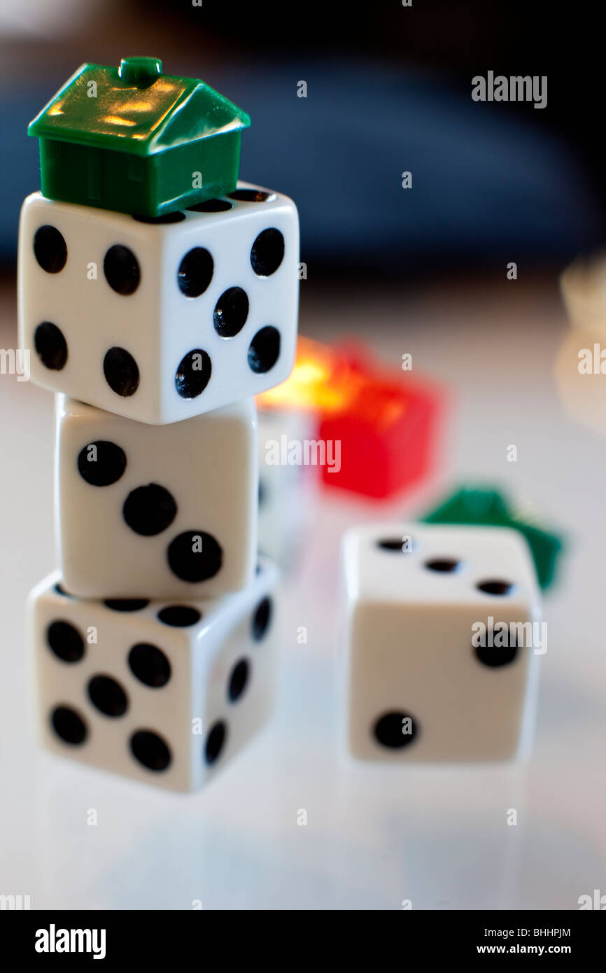 Stacked dice with Monopoly house - Stock Image