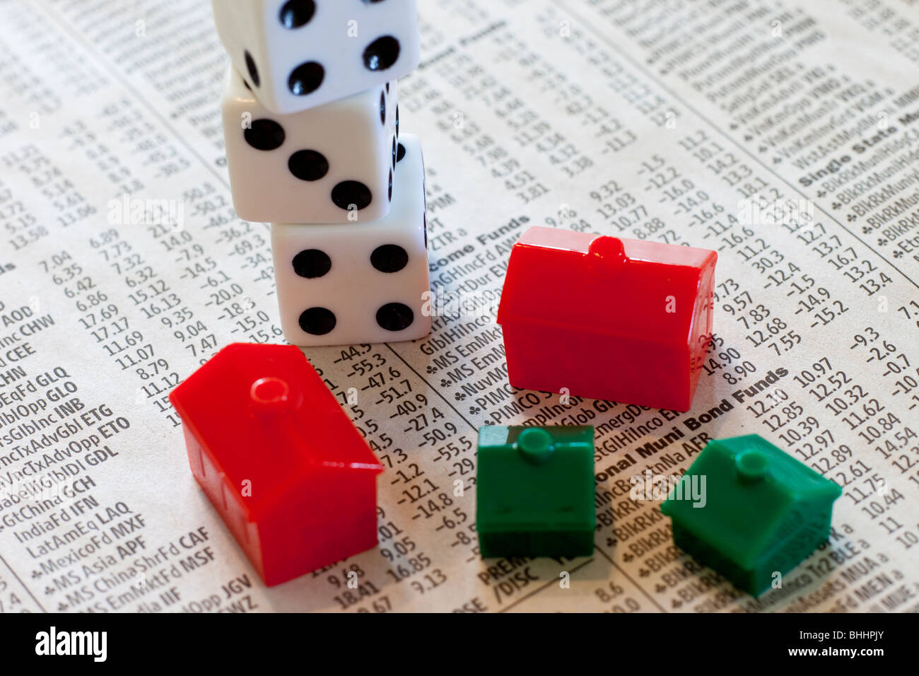 Dice, Monopoly houses and hotels on investment newspaper - Stock Image