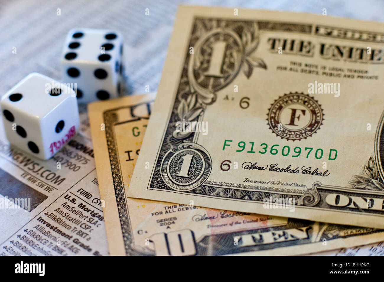 US Dollars, dice and investment newspaper - Stock Image