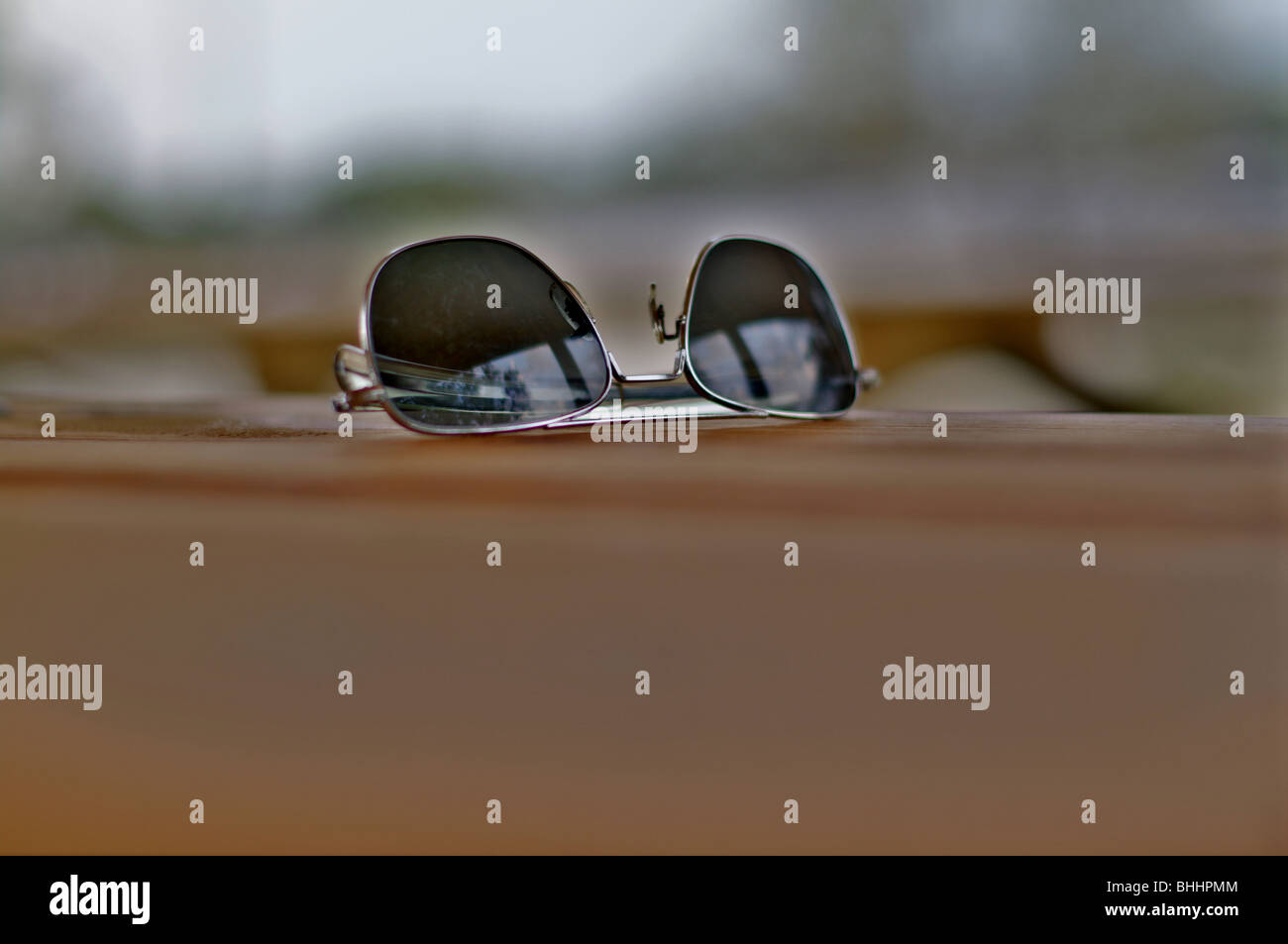 HDR capture of aviator sunglasses sitting on a picnic table with a very shallow depth of field. - Stock Image