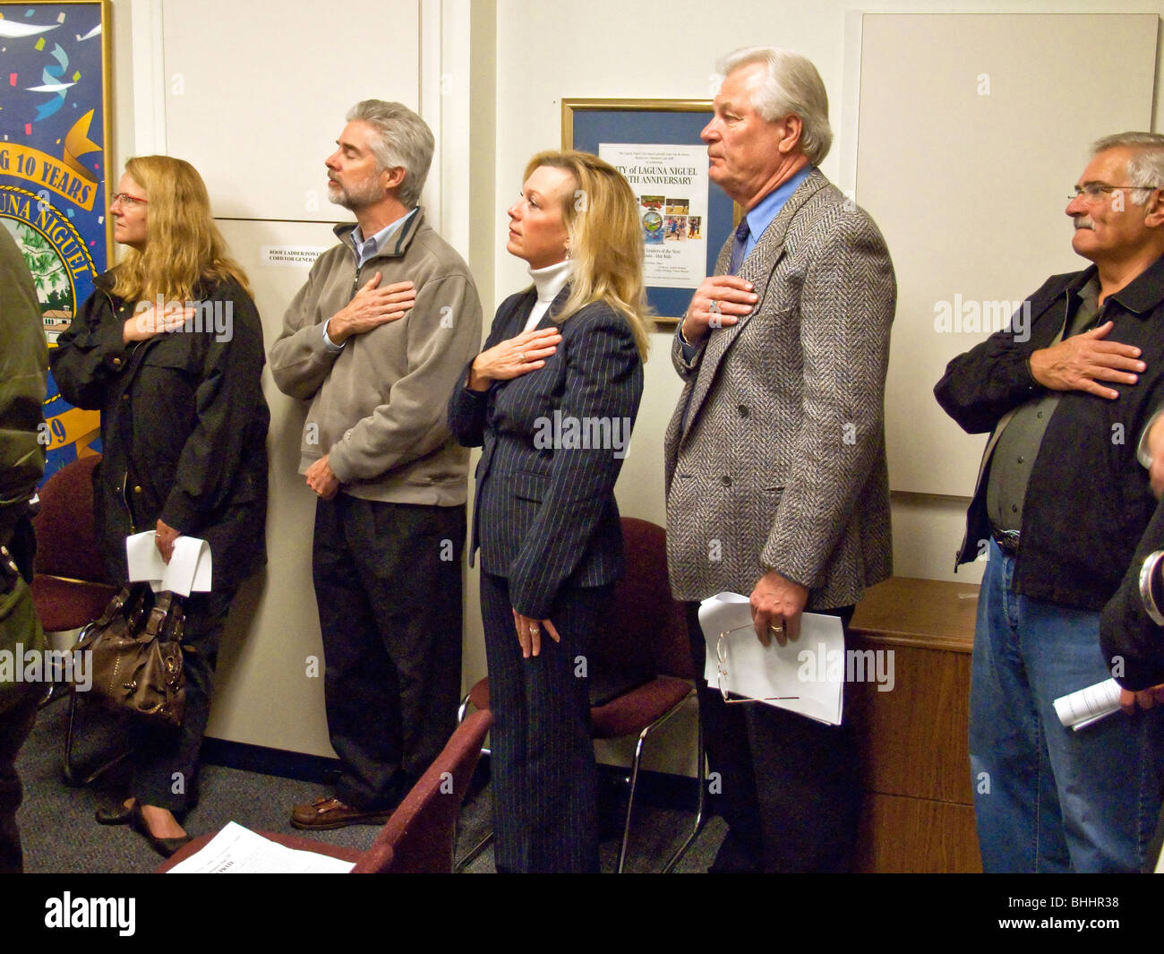 Hands over their hearts, local citizens recite the Pledge of Allegiance at the opening of a city council meeting - Stock Image