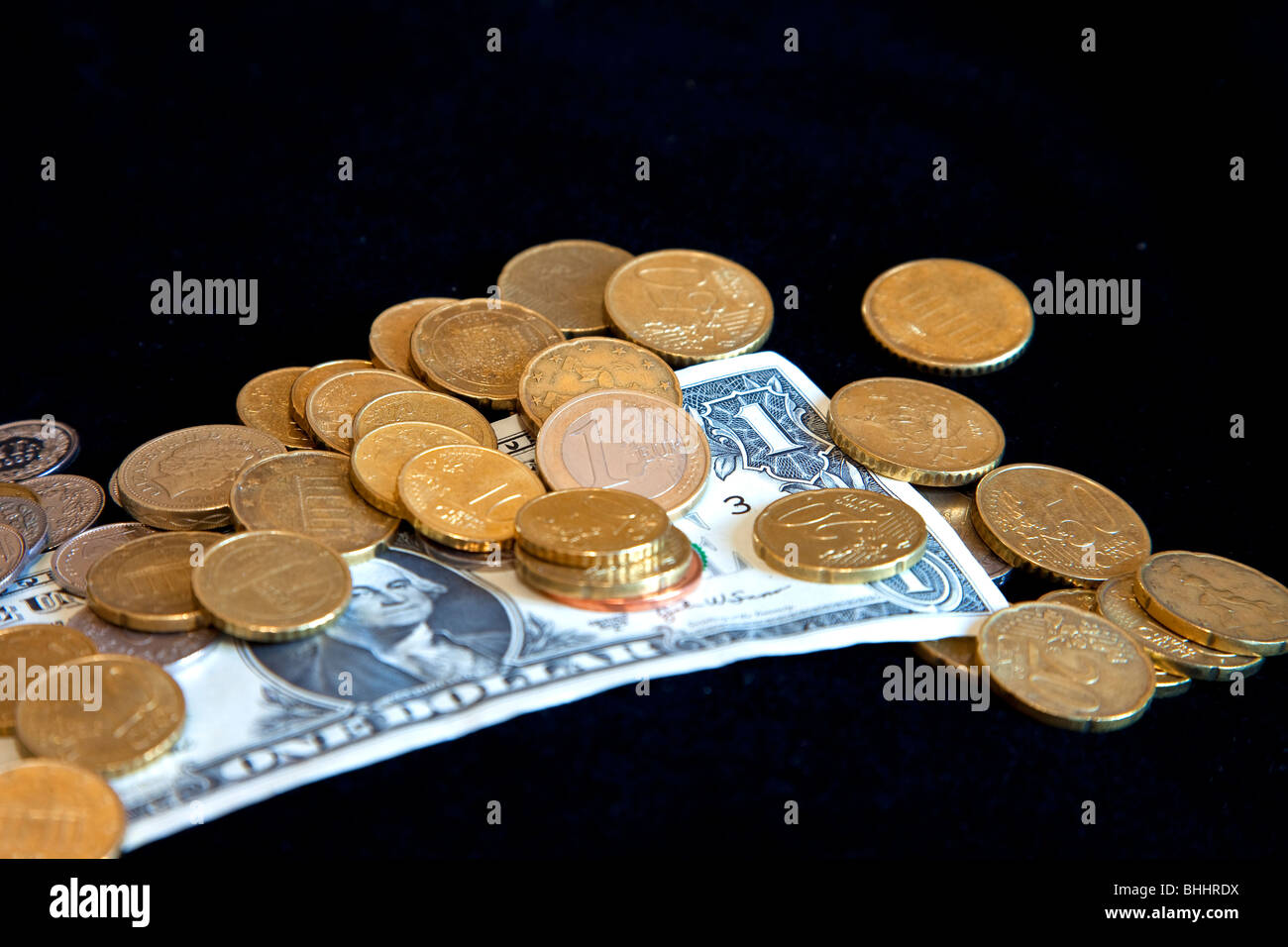Euro coins on a US dollar with black background - Stock Image