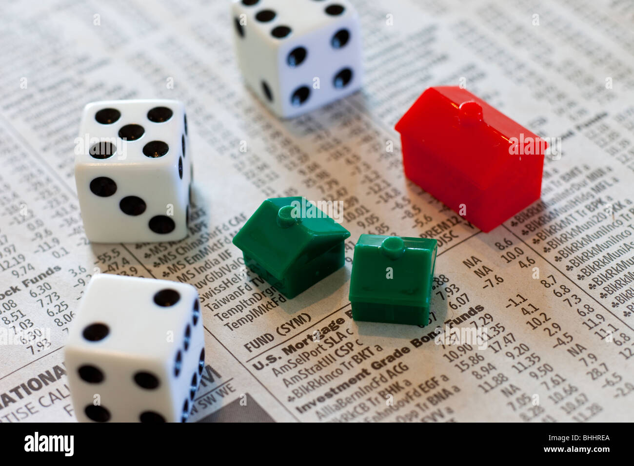 Dice, Monopoly houses and hotel on investment newspaper - Stock Image
