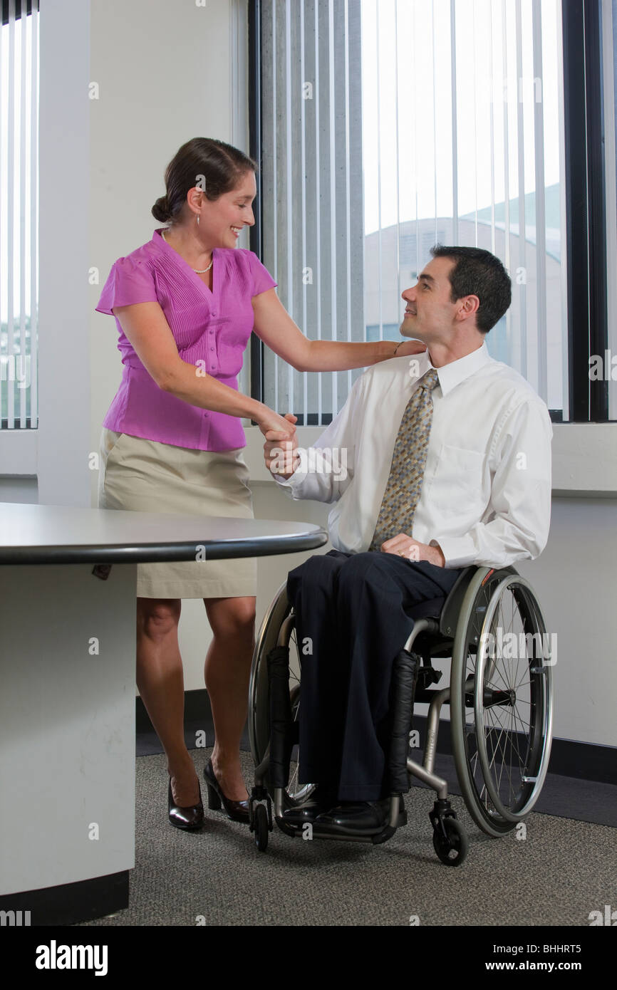 Handicapped businessman holding hands of his secretary - Stock Image