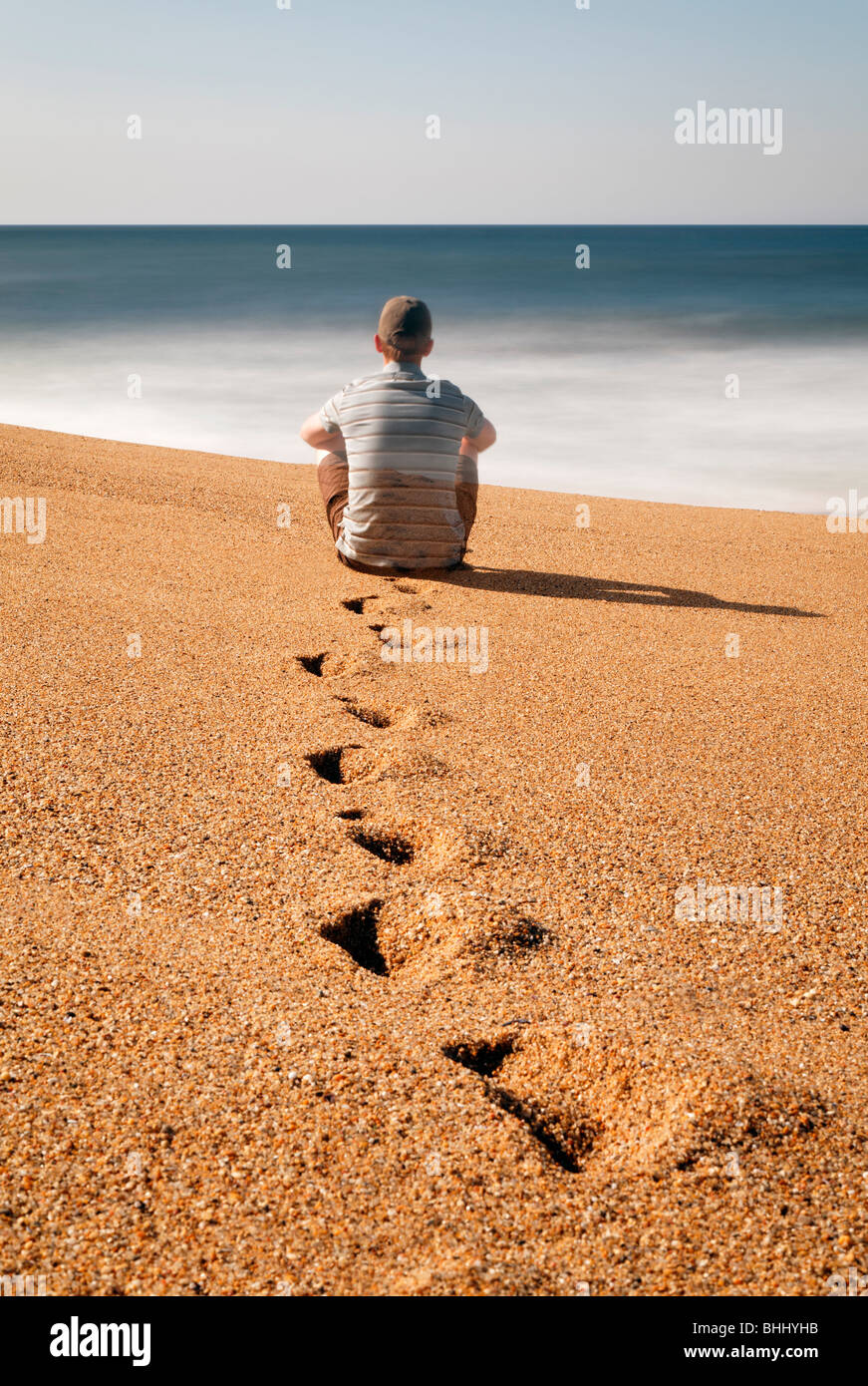 Man sitting on beach, looking out to sea - Stock Image