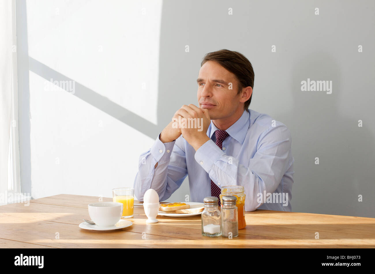 man in thoughts after breakfast - Stock Image