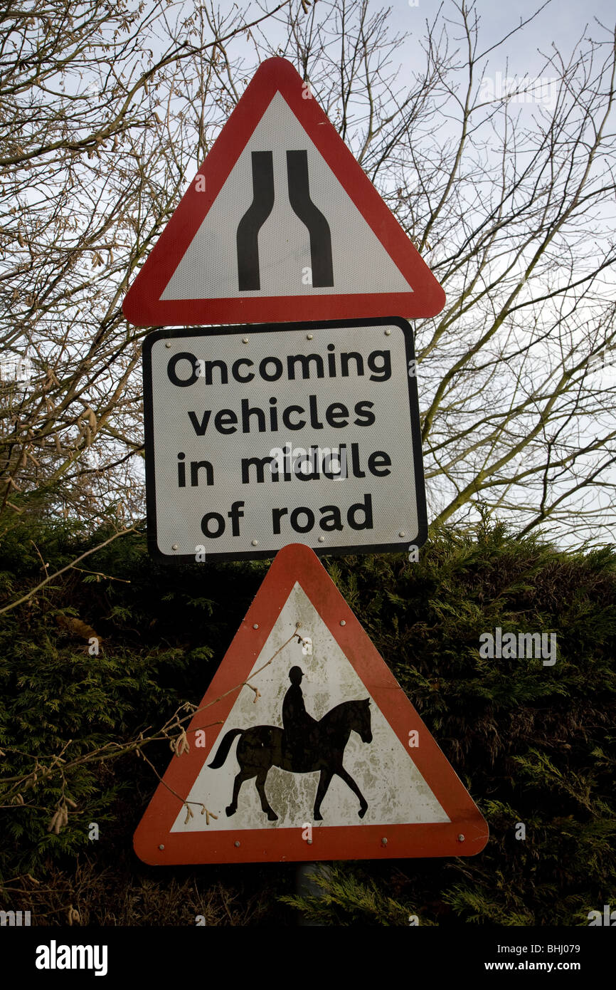 Multiple road sign hazards, road narrows, oncoming vehicles in middle of road, horse riders - Stock Image