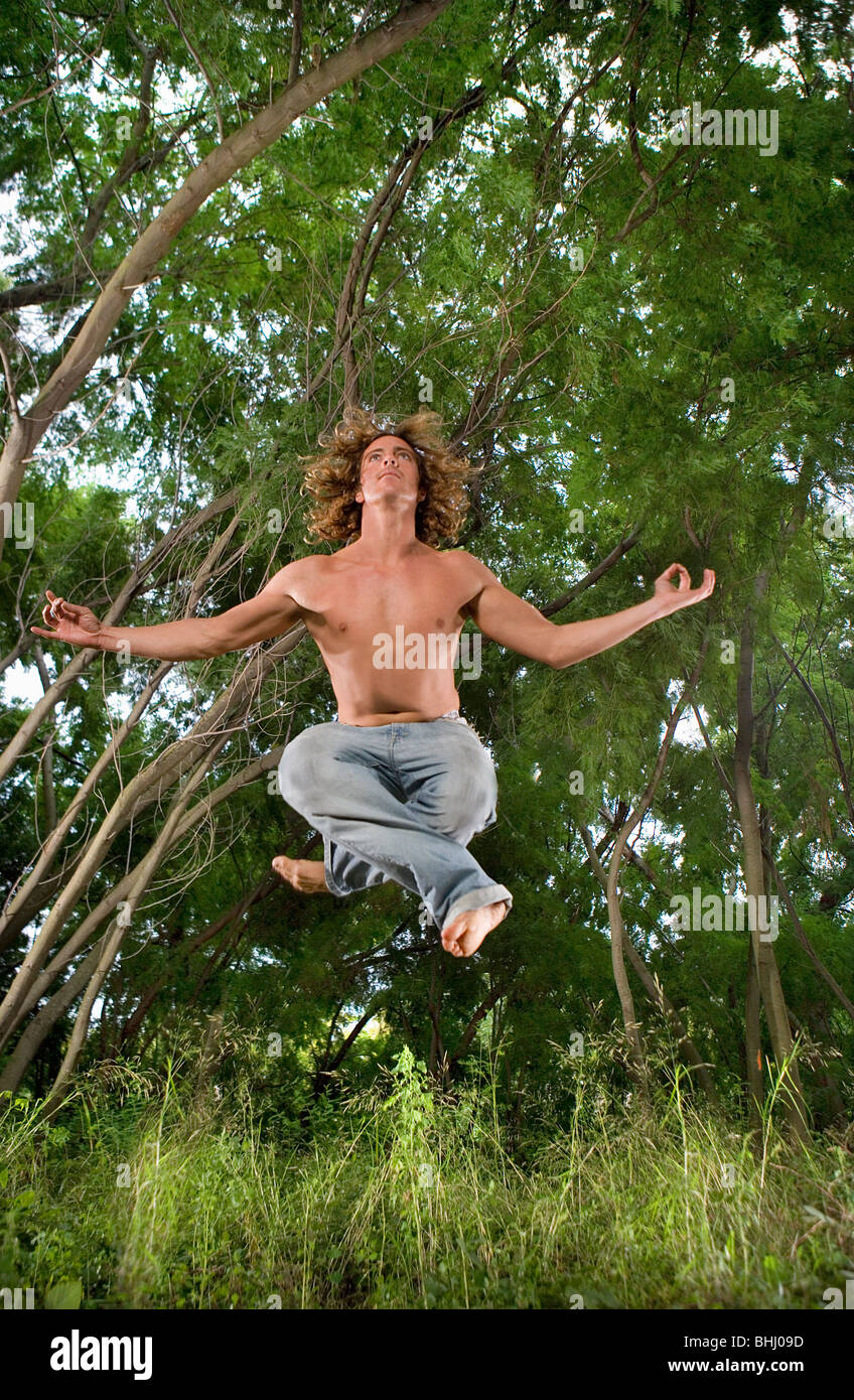 young man zen floats in forest - Stock Image