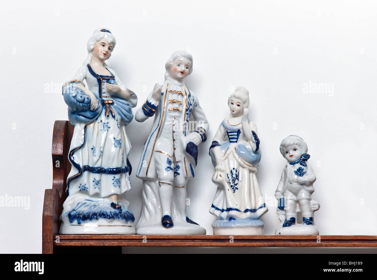 A set of small blue and white china period figurines on a shelf - Stock Image