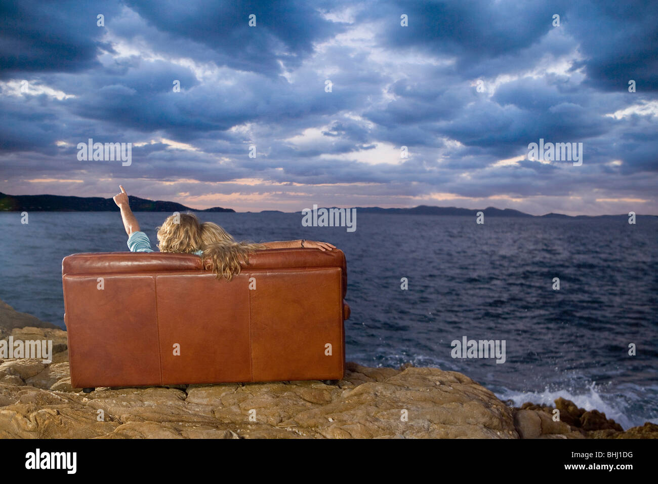couple on couch look at sea sky - Stock Image
