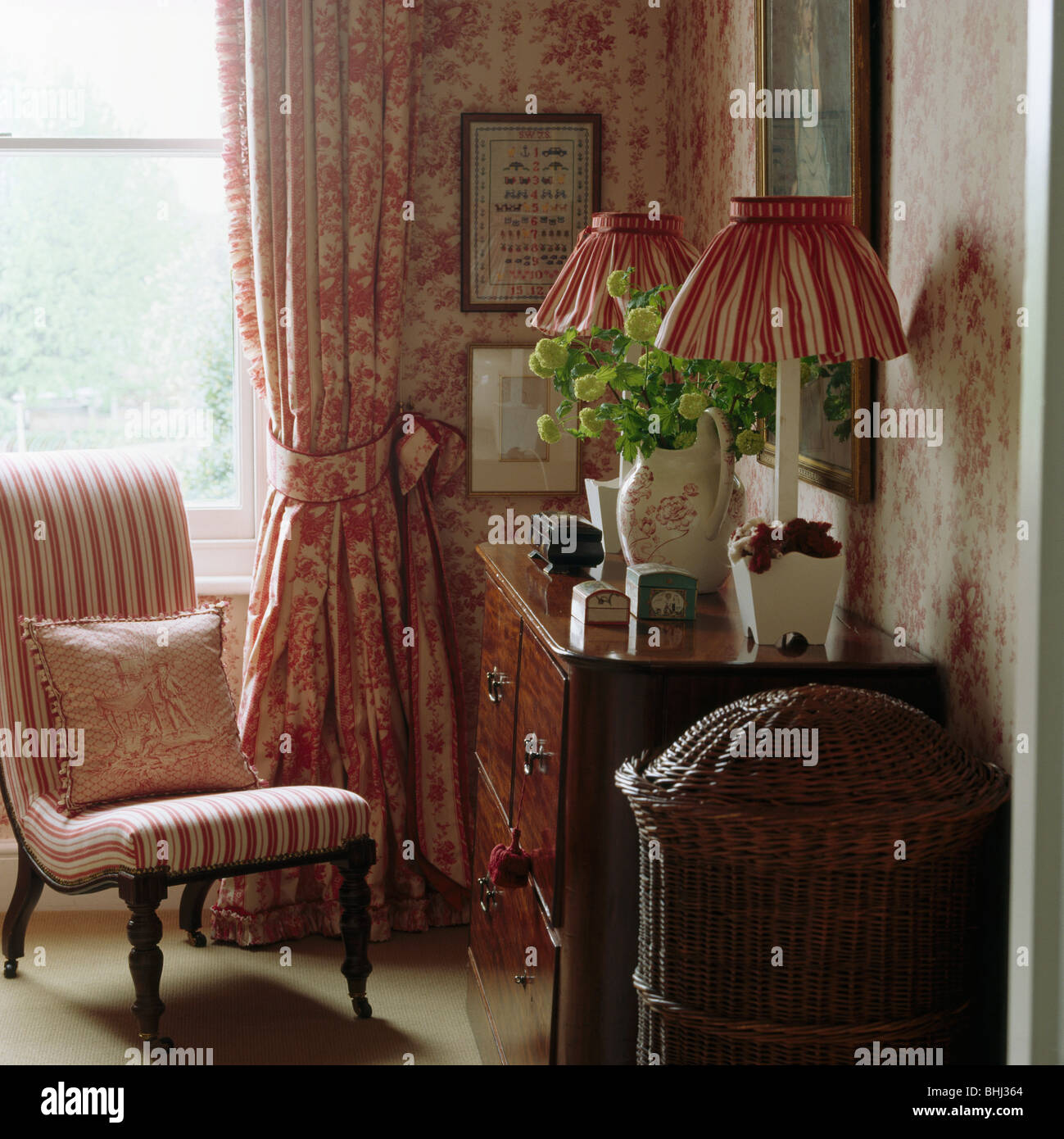 Pink Striped Upholstered Chair In Front Of Window With Pink Floral Curtain  In Corner Of Bedroom With Antique Chest Of Drawers