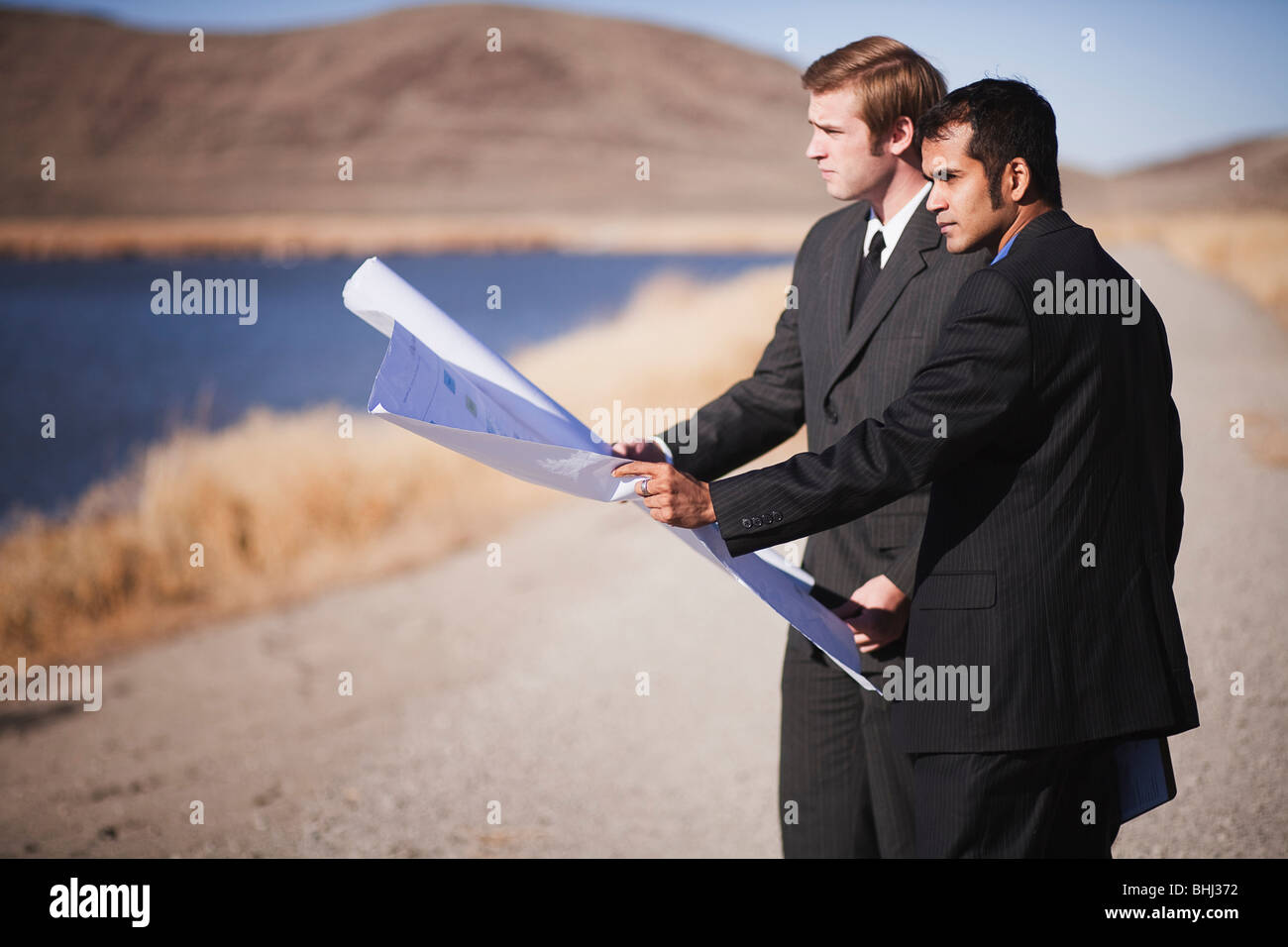 2 men with blueprints looking over water - Stock Image