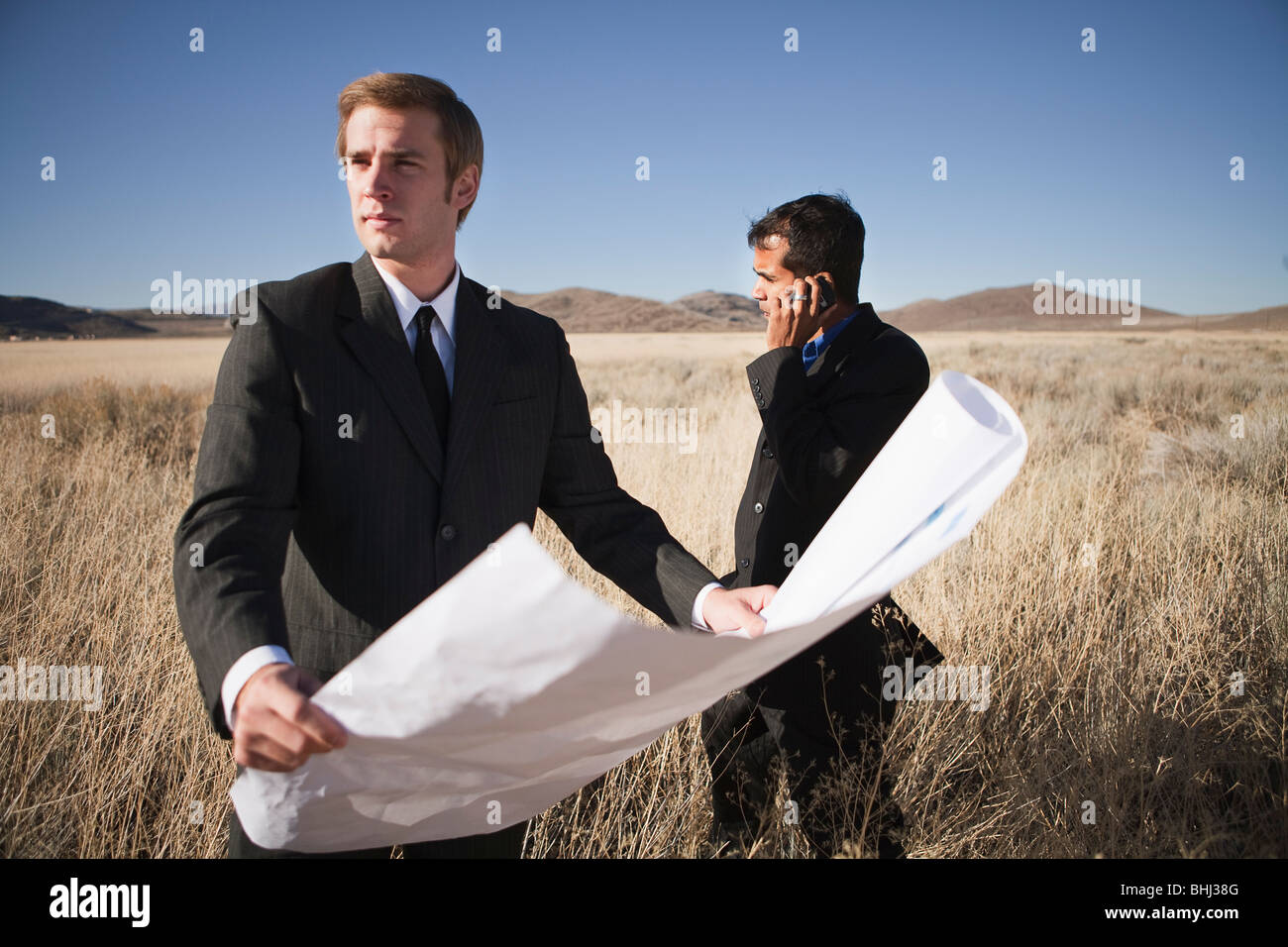 2 men with plans in field, one on phone - Stock Image