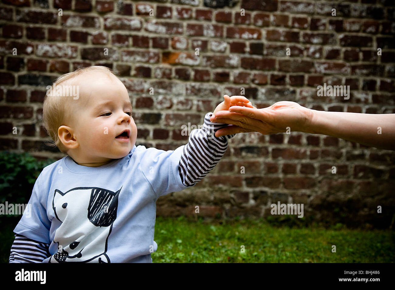 baby touches hand - Stock Image