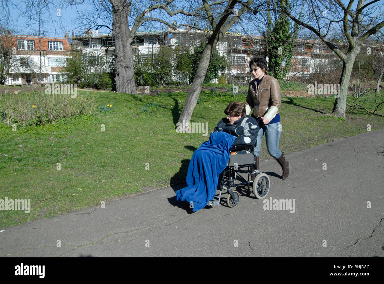 UK WOMAN CARING FOR A LADY IN A WHEELCHAIR - Stock Image