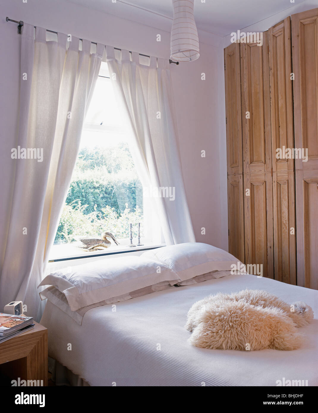 White curtains on window above bed with bedlinen and ...