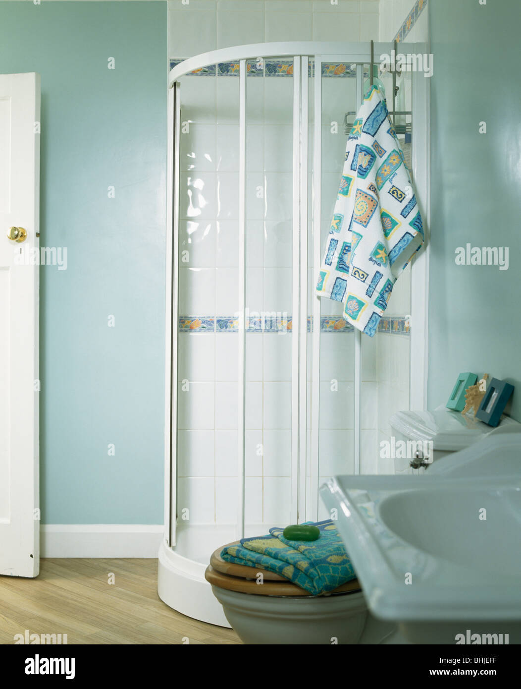 Glass shower cabinet in corner of pastel blue bathroom Stock Photo ...