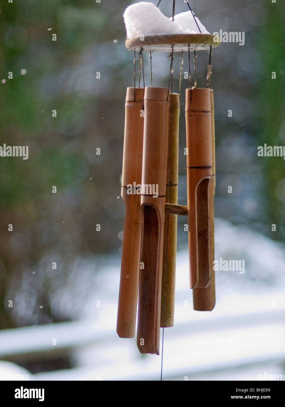 bamboo wind chimes hanging from roof in garden in winter with snow - Stock Image