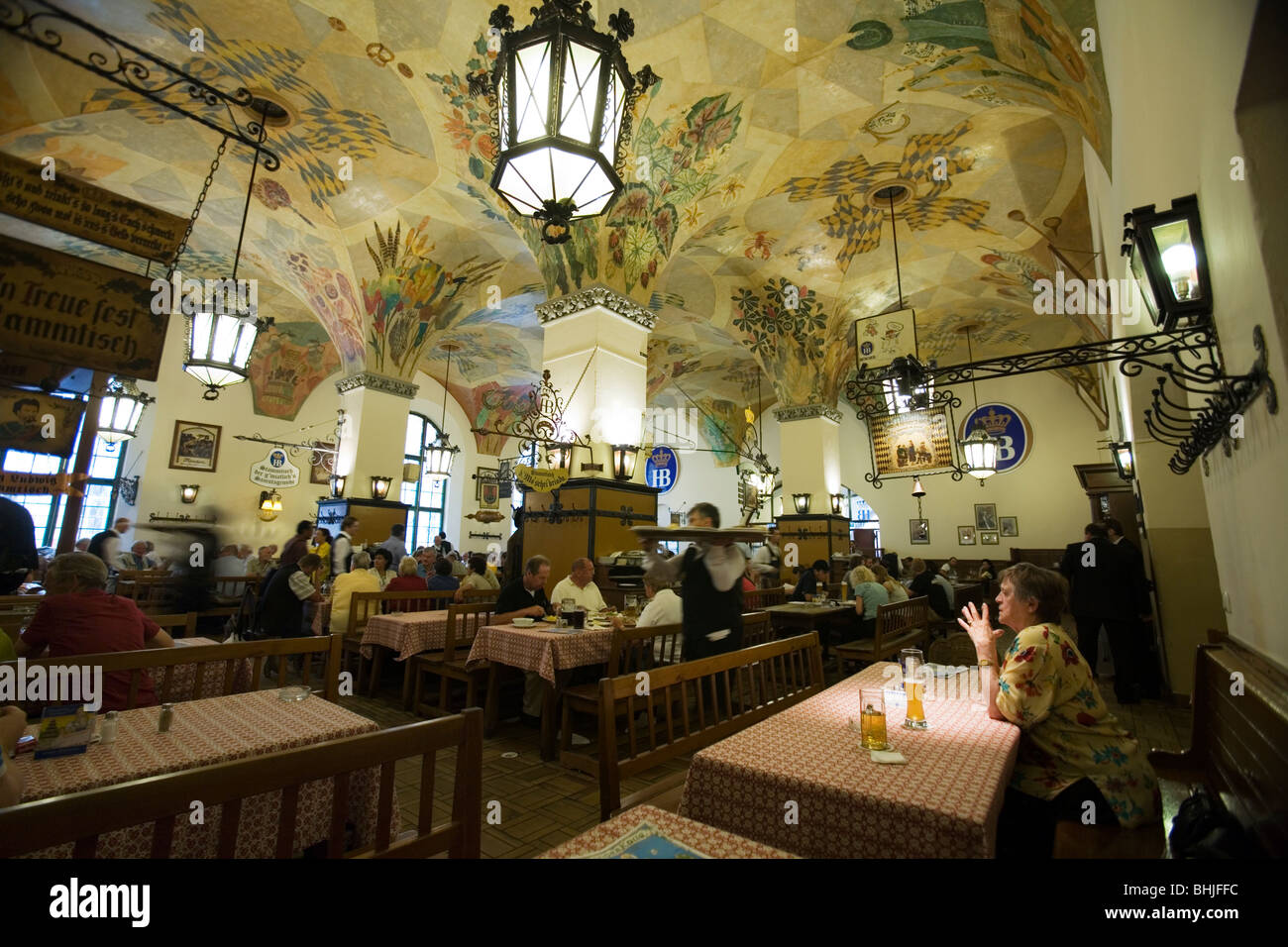 A woman at her table looking a the elaborated ceiling at the Hofbrauhaus am Platzl. Munich, Germany - Stock Image