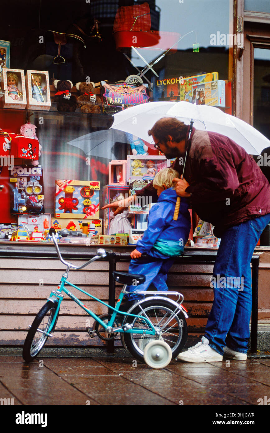 Dad and son window shopping at toy store in the rain - Stock Image