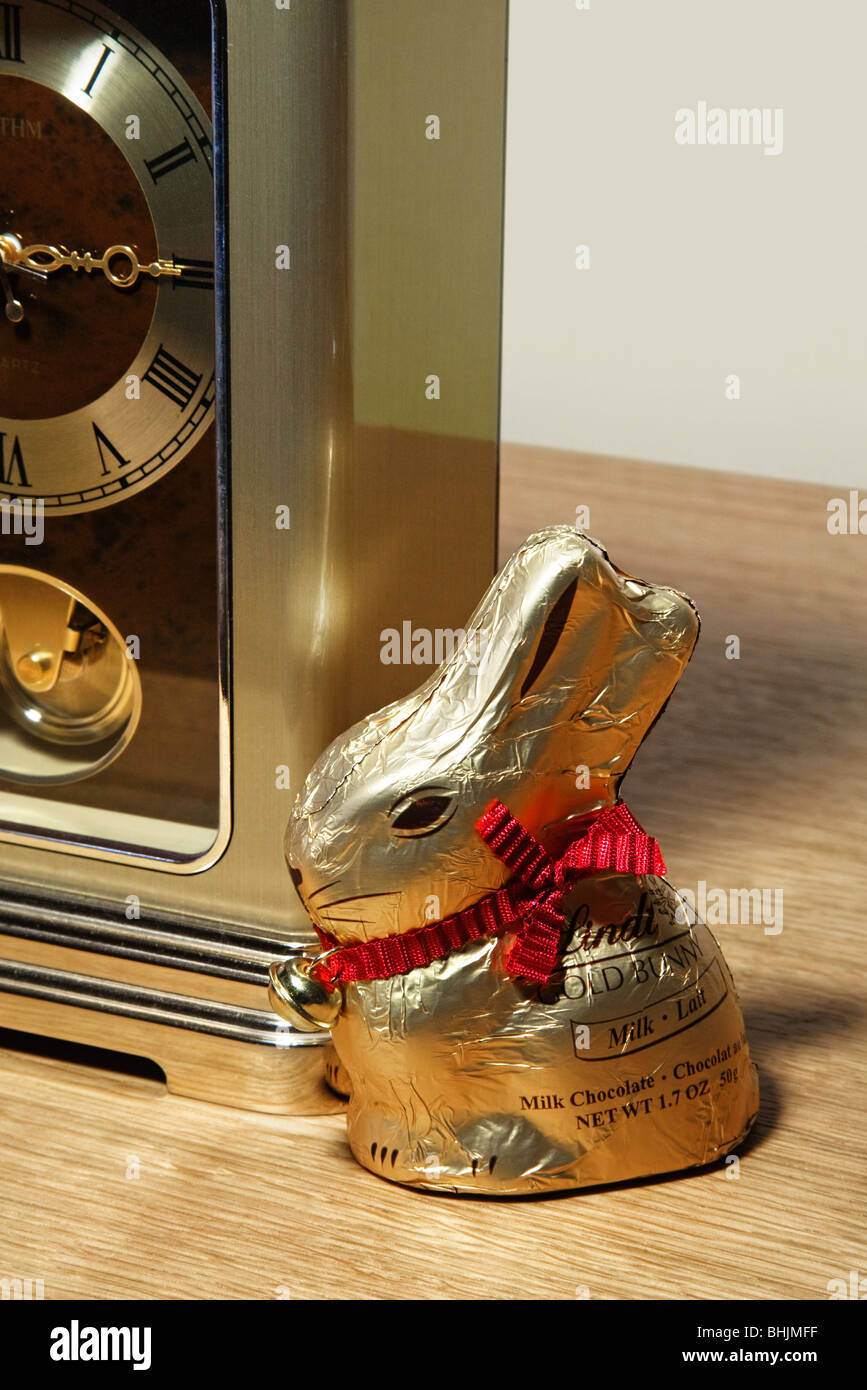 A Lindt gold foil wrapped chocolate Easter rabbit sitting next to a clock. - Stock Image