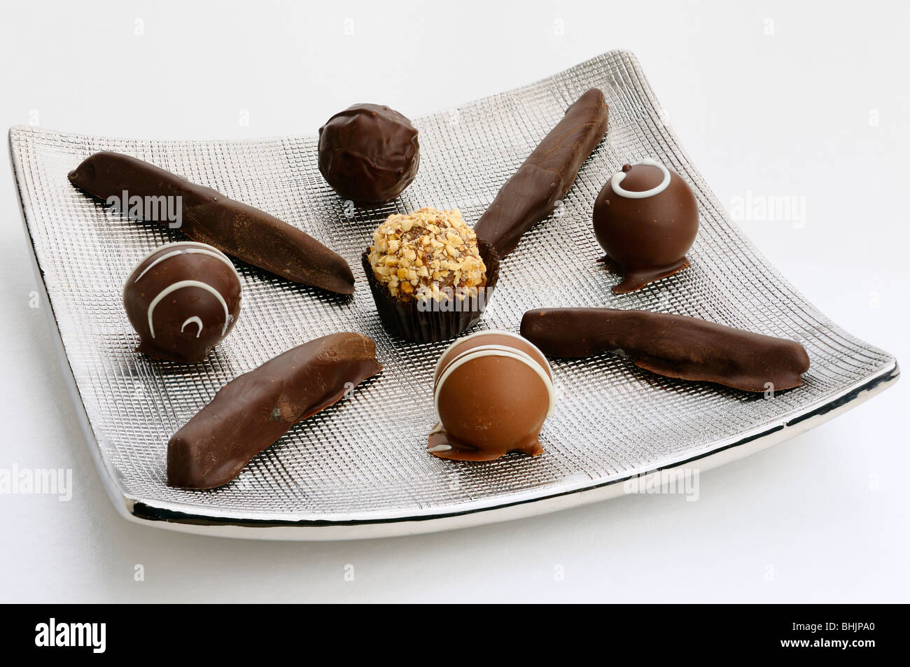 Hand made chocolate truffles and candied orange rind on a silver plate on white - Stock Image