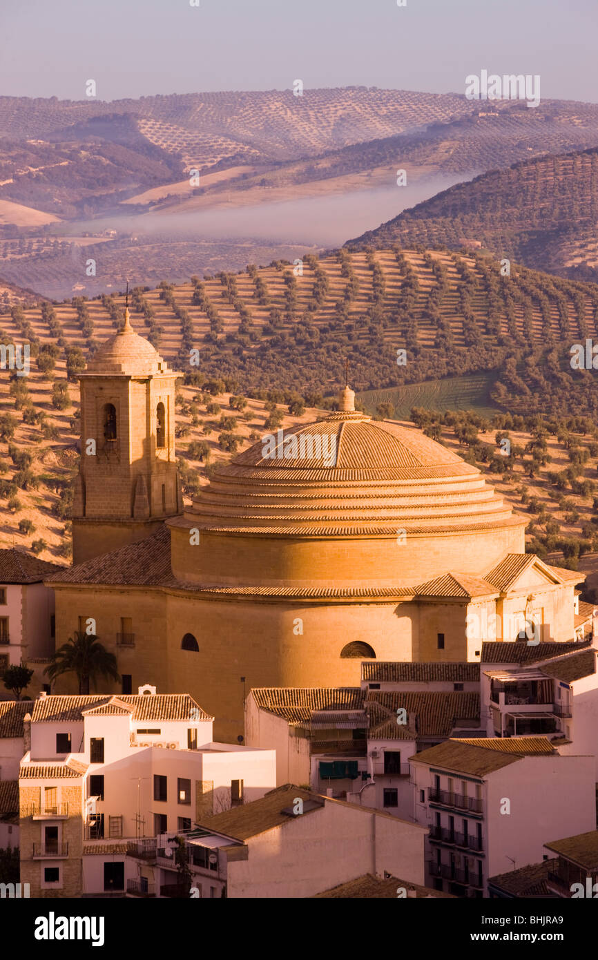 spain, Andalucia, Montefrio Elevated view over town church and surrounding olive fields in golden morning light - Stock Image