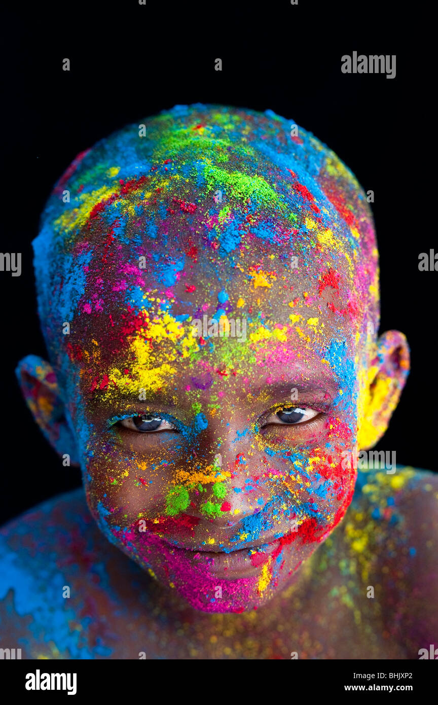 Happy young Indian boy covered in coloured powder pigment against a black background - Stock Image