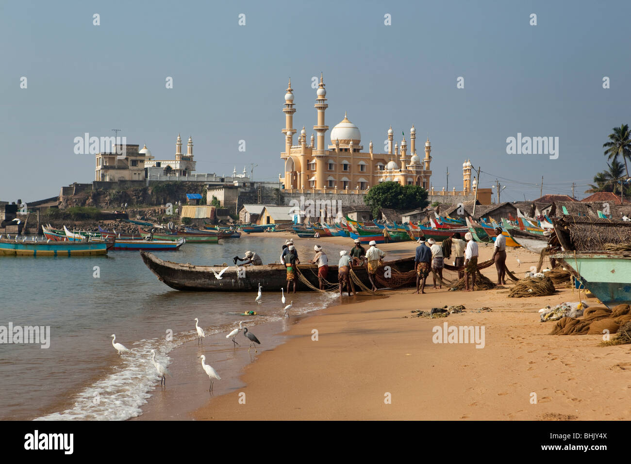 India, Kerala, Kovalam, Vizhinjam village fishermen unloading fishing boats on beach in front of mosque - Stock Image