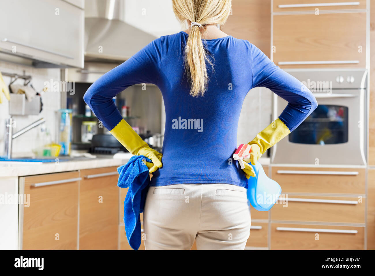 rear view of woman with yellow gloves in kitchen doing housework - Stock Image