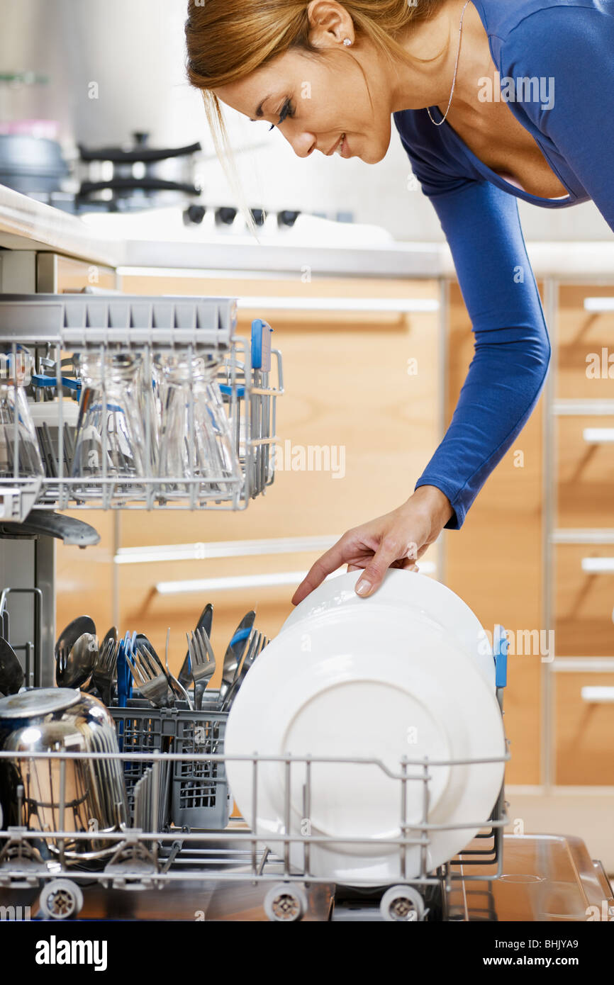 side view of young woman in kitchen doing housework - Stock Image