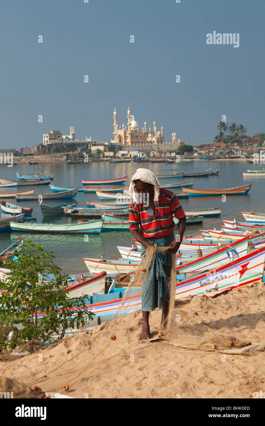 India, Kerala, Kovalam, Vizhinjam village fisherman tending to his fishing nets - Stock Image
