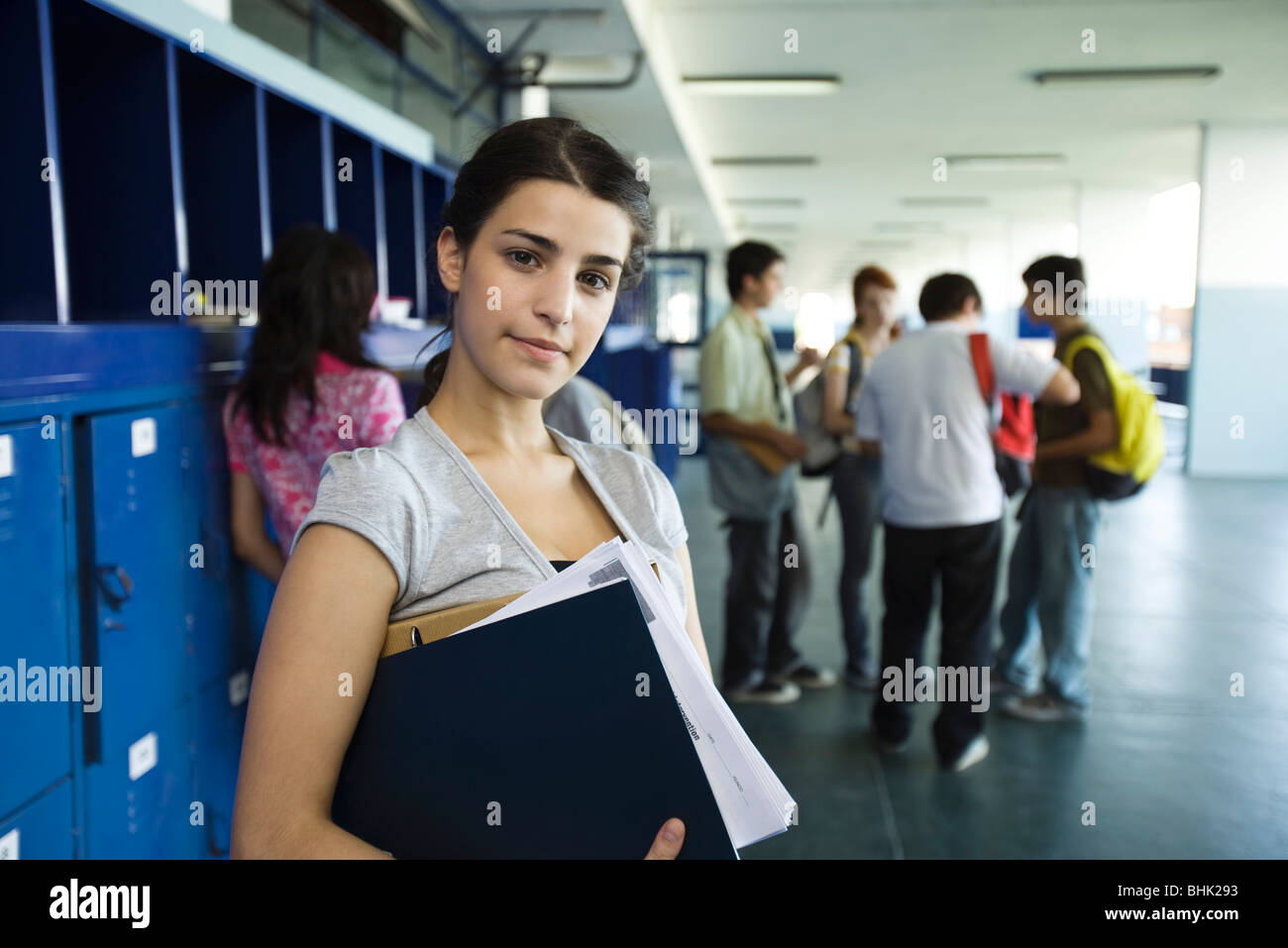 Female high school student standing in hall lined with lockers - Stock Image