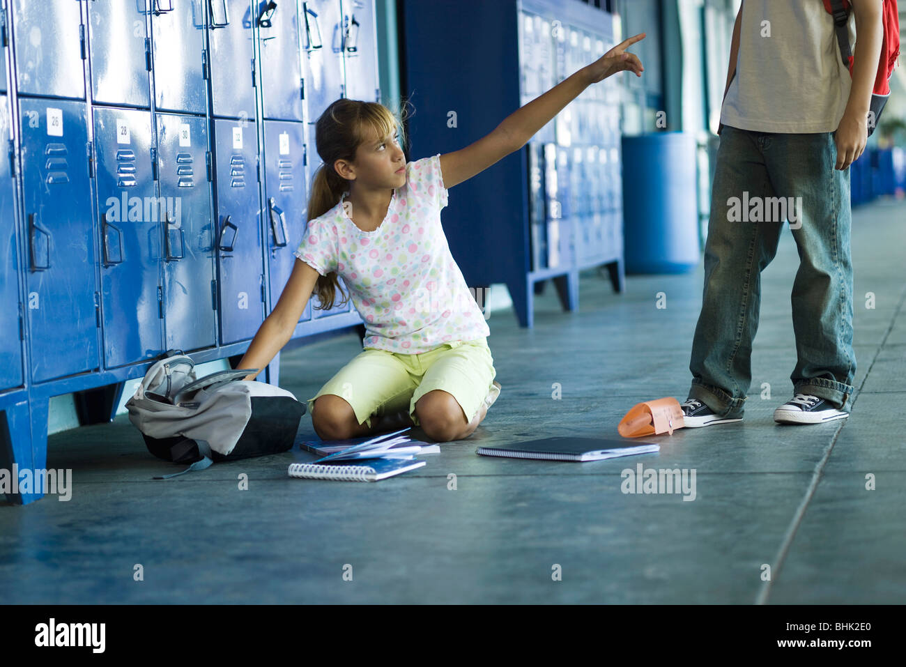 Female junior high student sitting on floor pointing angrily up at boy standing over her - Stock Image
