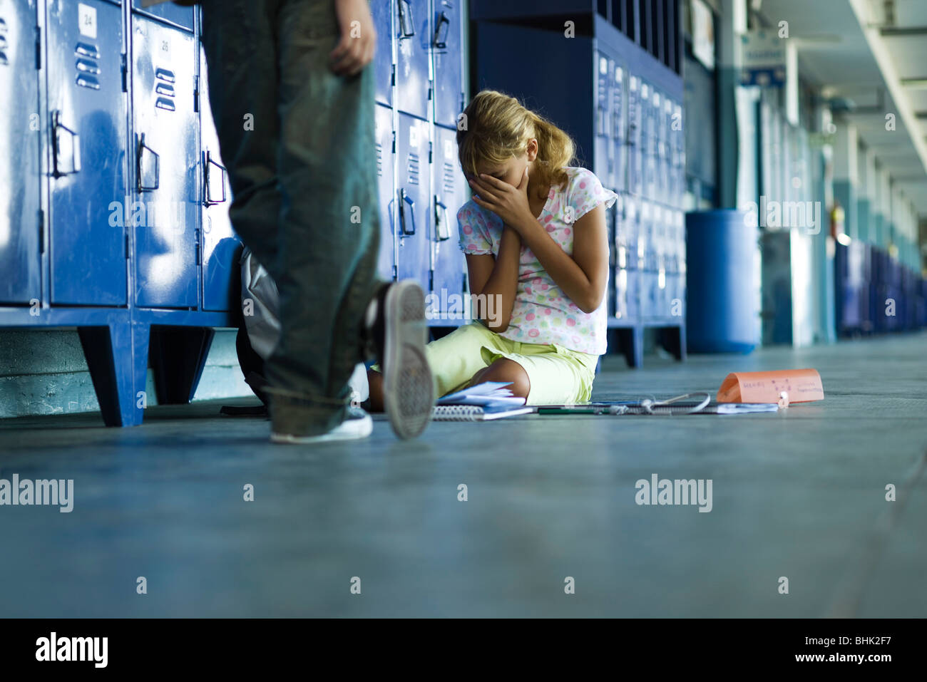 Female junior high student sitting on floor holding head in hands, boy standing smugly nearby - Stock Image