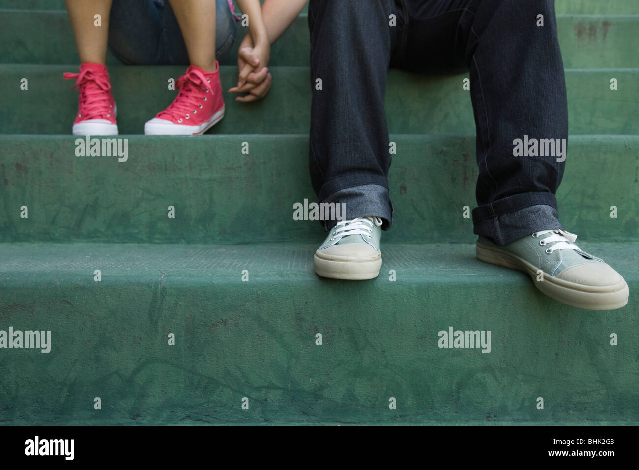 Teenage couple sitting together on steps, low sectionStock Photo