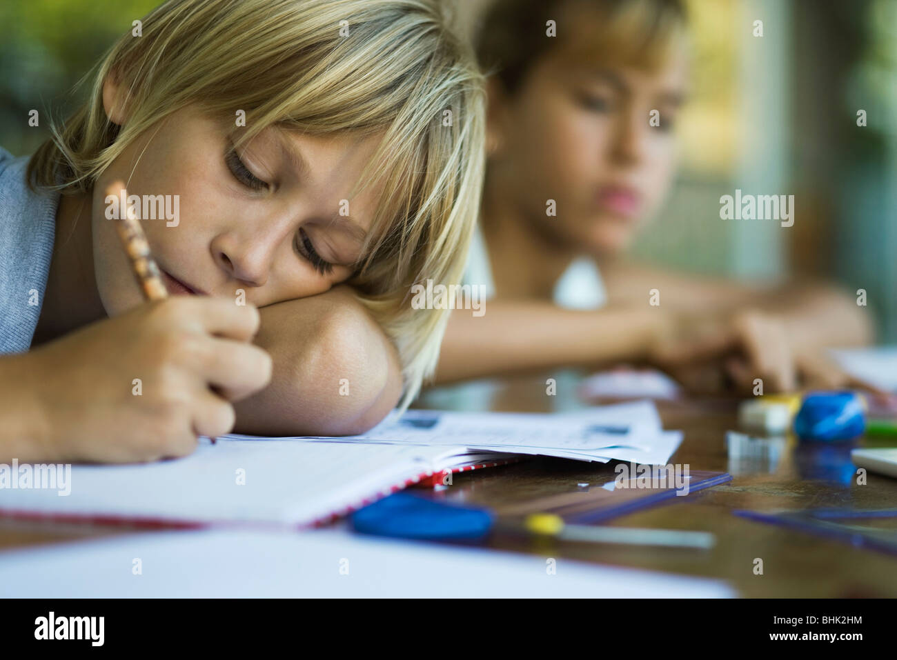 Junior high student resting head on arm while writing assignment - Stock Image