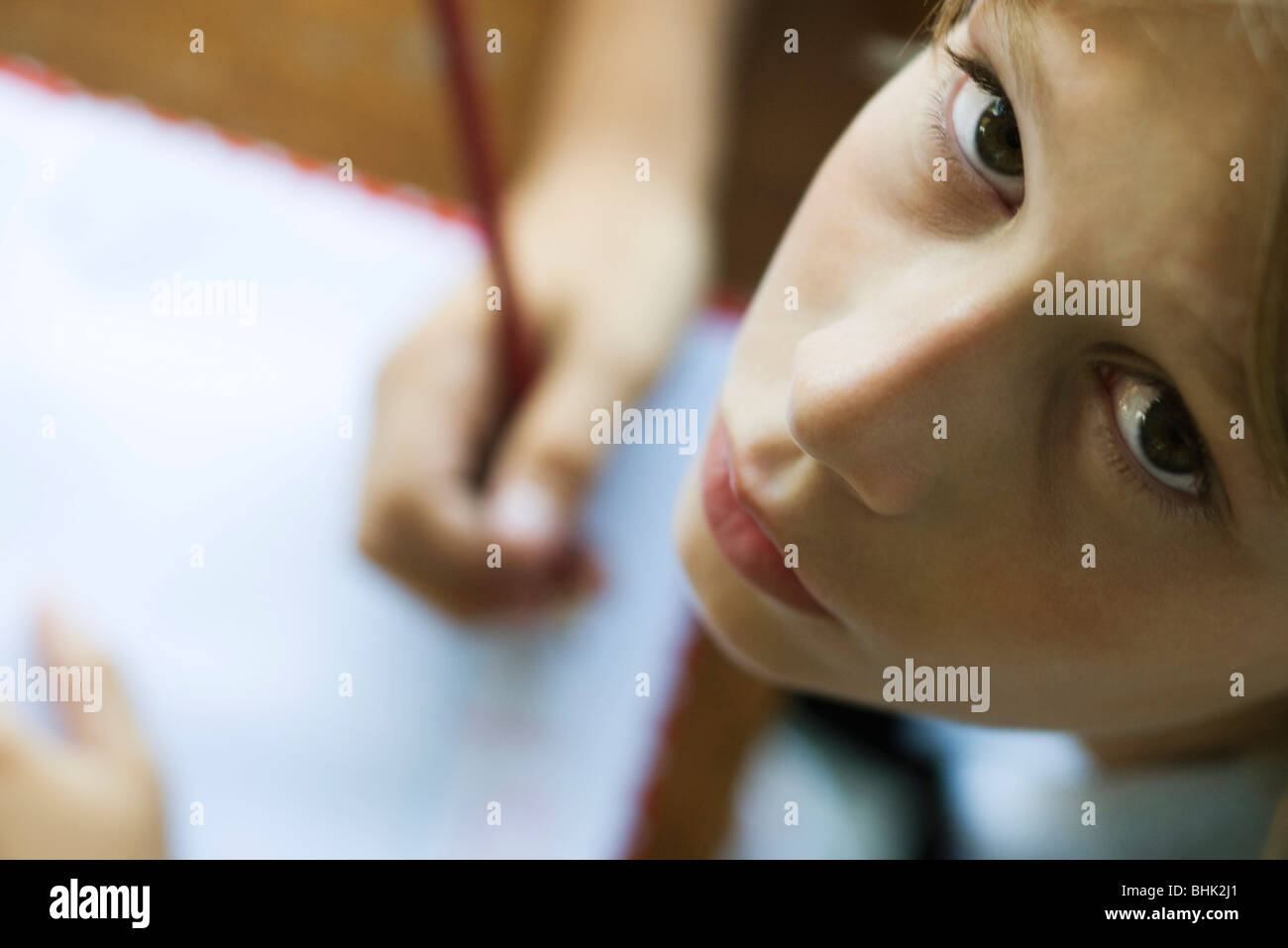 Boy writing in notebook, pausing work to look up at camera - Stock Image