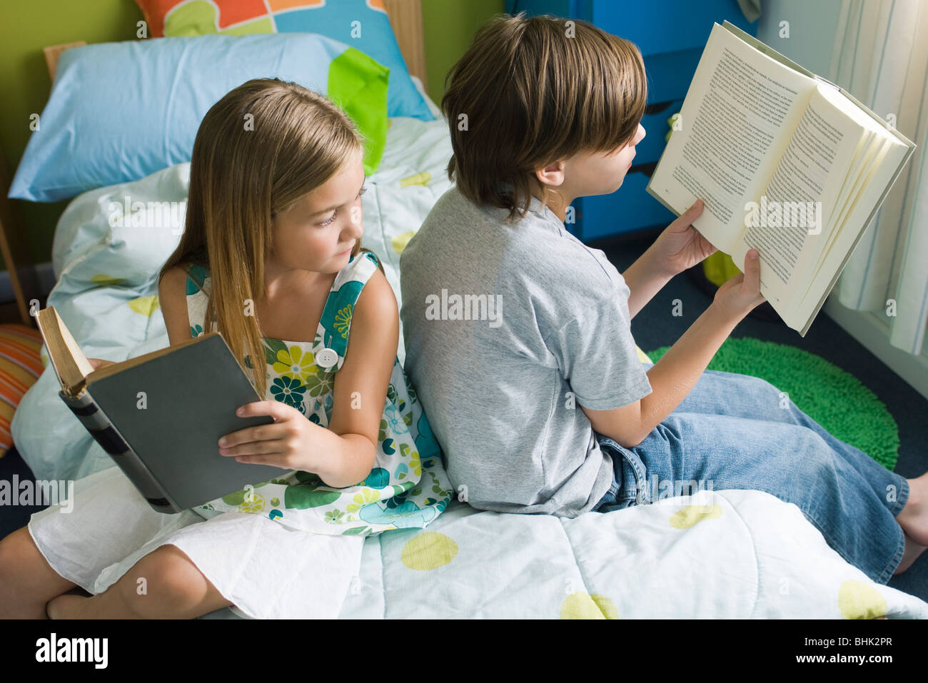 Siblings reading together, girl glancing over shoulder at brother's book - Stock Image