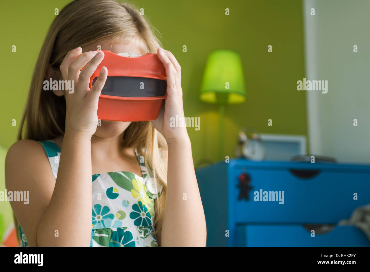 Girl looking through toy viewfinder - Stock Image