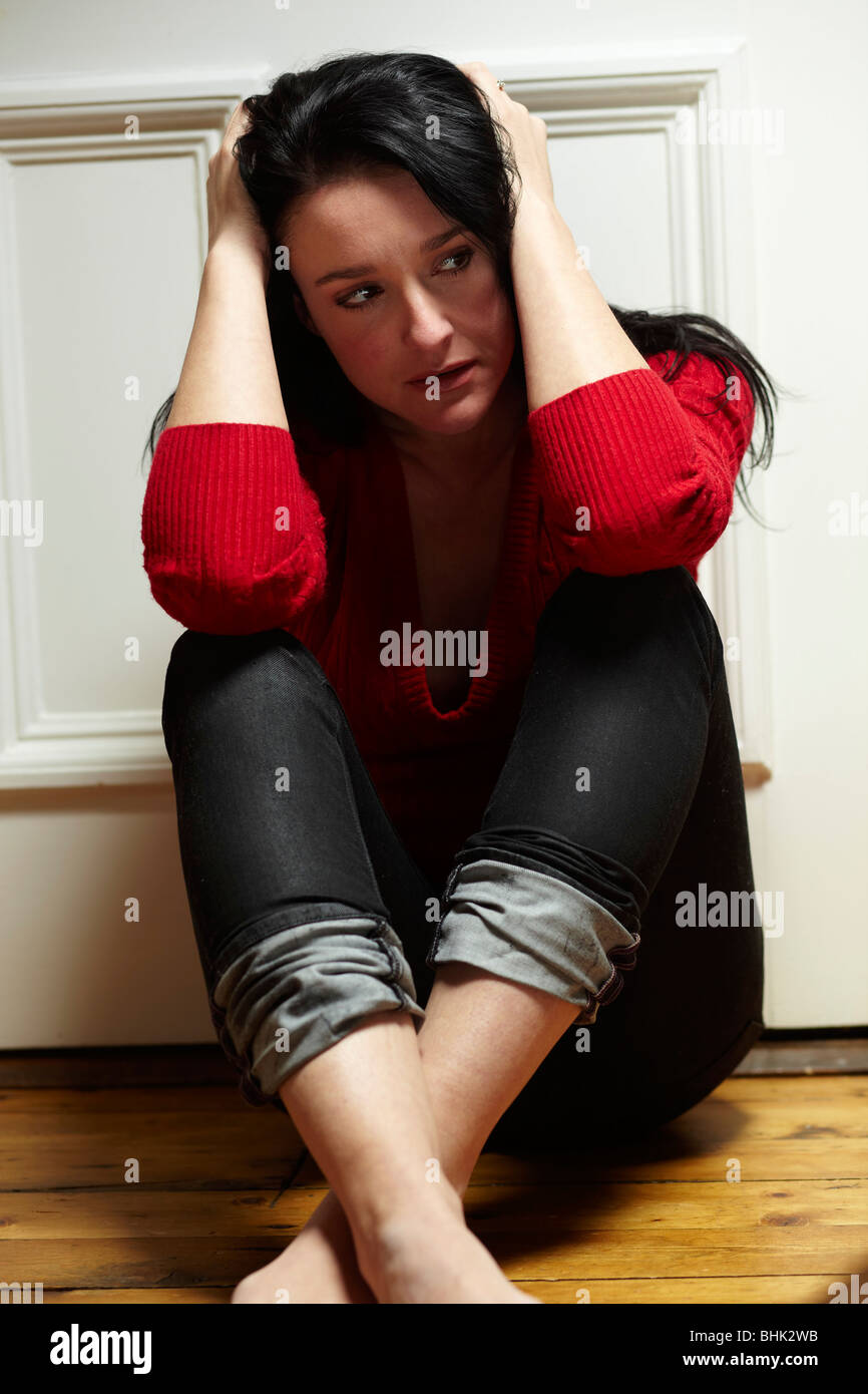 Stressed woman sat on floor - Stock Image